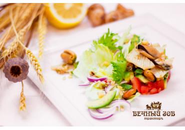 Салат из мидий и кальмаров с ростками сои, ломтиками авокадо, помидорами конкосе, сдобренный растительным маслом и соком лимона